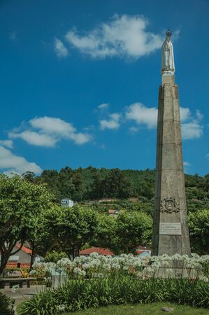 Marble statue of Our Lady on stone pillory at flowered garden, in a sunny day at Seia. On foothill mountains, this friendly town in eastern Portugal is also known for its delicious artisanal cheese. Stok Fotoğraf