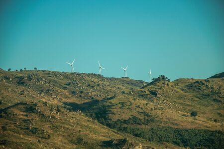 Hilly landscape covered by rocks and undergrowth with some wind turbines, on sunset at the highlands of Serra da Estrela. The highest mountain range in continental Portugal, with astonishing scenery.