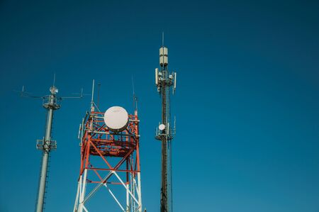 Telecommunication cellular network towers with antennas in a base transceiver station and blue sky at Guarda. This friendly and well-kept medieval town is the highest in the continental Portugal. Stock fotó