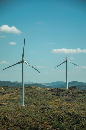 Wind turbines for electric power generation over green hilly landscape with rocks, in a sunny day at Sortelha. One of the most astonishing and well preserved medieval villages in all Portugal.
