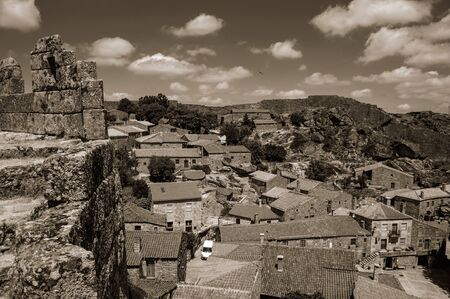 Pathway over thick stone wall next to rooftops of old houses at the Sortelha Castle. One of the most astonishing and well preserved medieval villages in all Portugal. Black and white photo.