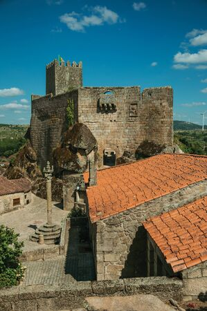 Stone Castle with tower over rocky hill and old house next to square with pillory, in a sunny day at Sortelha. One of the most astonishing and well preserved medieval villages in all Portugal. Stock Photo