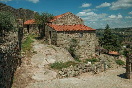 Casa gótica de piedra en el callejón en pendiente sobre terreno rocoso y pared en el fondo, en un día soleado en Sortelha. Uno de los pueblos medievales más asombrosos y mejor conservados de todo Portugal. Foto de archivo