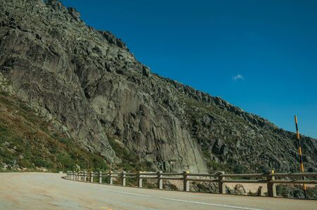 Concrete parapet on edge of road passing through rocky landscape in a sunny day, at the highlands of the Serra da Estrela. The highest mountain range in continental Portugal, with astonishing scenery.