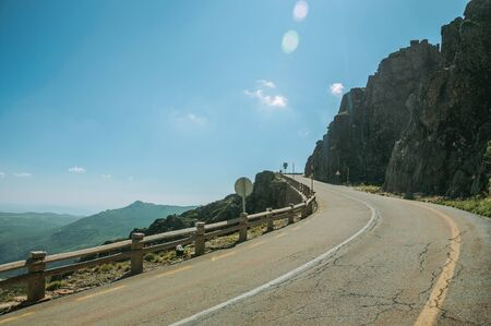 Curve road with concrete parapet passing through rocky landscape in a sunny day, at the highlands of the Serra da Estrela. The highest mountain range in continental Portugal, with astonishing scenery.