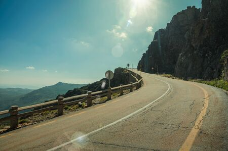 Curve road with concrete parapet passing through rocky terrain, at the highlands of the Serra da Estrela. The highest mountain range in continental Portugal, with astonishing scenery. Retouched photo. Stock Photo