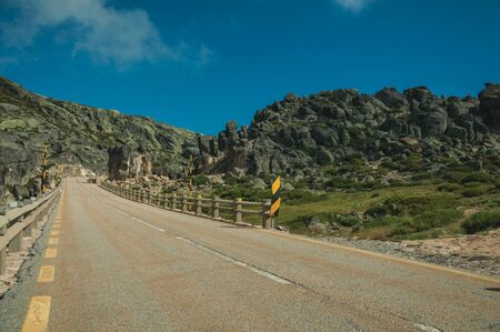 Long roadway passing through rocky landscape in a sunny day, at the highlands of the Serra da Estrela. The highest mountain range in continental Portugal, with astonishing scenery. 版權商用圖片 - 128119225