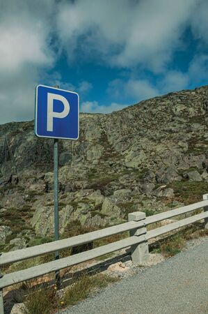 Roadway with concrete parapet on rocky landscape and PARKING traffic signpost, at the highlands of Serra da Estrela. The highest mountain range in continental Portugal, with astonishing scenery.