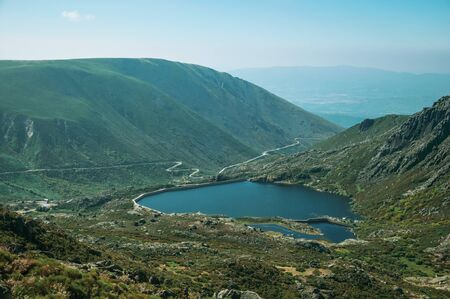 Blue fresh water at dam lake on hilly landscape covered by rocks and brushwood, on the highlands at the Serra da Estrela. The highest mountain range in continental Portugal, with astonishing scenery. 写真素材