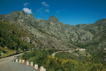 Long roadway passing through rocky landscape with green bushes in a sunny day, at the highlands of Serra da Estrela. The highest mountain range in continental Portugal, with astonishing scenery. Фото со стока