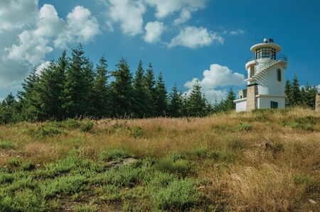 Unusual lighthouse on top of hill covered by green grass and trees, in a sunny day at the highlands of Serra da Estrela. The highest mountain range in continental Portugal, with astonishing scenery.