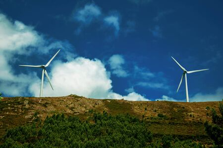Large propeller blades from two wind generators of electric power on hilly landscape at Serra da Estrela. The highest mountain range in continental Portugal, with astonishing scenery. Retouched photo.