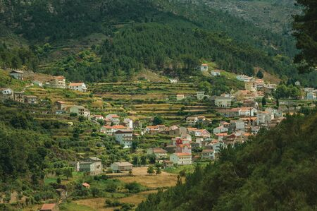 Hügelige Landschaft mit Bäumen und terrassierten Feldern mit den Dächern von Alvoco da Serra darunter. Ein süßes Dorf, das sich an einem steilen Tal im Hochland Serra da Estrela im Osten Portugals festhält. Standard-Bild