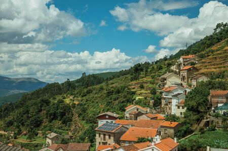 Charming houses going up on the hilly landscape covered by trees and terraced fields at Alvoco da Serra. A cute village clinging on a steep valley in the Serra da Estrela highland on eastern Portugal.