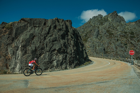 Serra da Estrela, Portugal - July 14, 2018. Curve on roadway passing through rocky landscape with cyclist, at the highlands of Serra da Estrela. The highest mountain range in continental Portugal. Редакционное