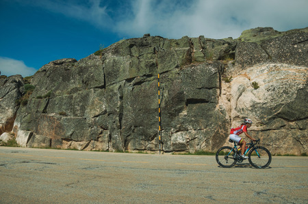 Serra da Estrela, Portugal - July 14, 2018. Cyclist on roadway passing through rocky landscape in a sunny day, at the highlands of Serra da Estrela. The highest mountain range in continental Portugal.
