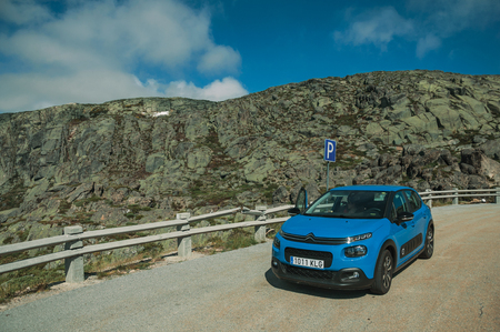 Serra da Estrela, Portugal - July 14, 2018. Car parked in the roadside on rocky landscape, at the Serra da Estrela ridge. The highest mountain range in continental Portugal, with astonishing scenery. Редакционное