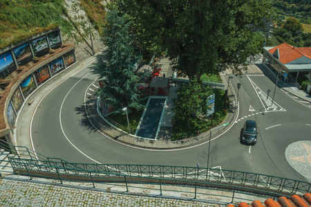Manteigas, Portugal - July 14, 2018. Sharp curve in a road around trees with car, in a sunny day at Manteigas. It is the genuine mountain village at the Serra da Estrela on eastern Portugal. Editorial
