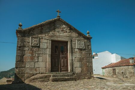 Medieval chapels of Saint Anthony and Calvary on a cobblestone square, in a sunny day at Belmonte. A cute small town, birthplace of the navigator Pedro Alvares Cabral, on eastern Portugal.
