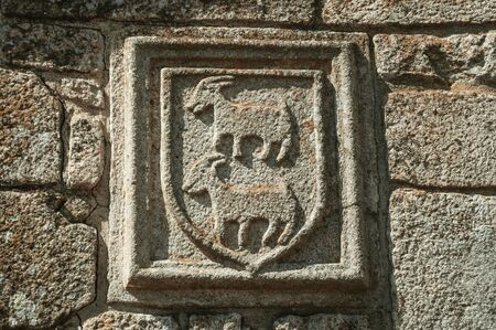 Charming family coat of arms carved on stone in a wall of medieval chapel, in a sunny day at Belmonte. A cute small town, birthplace of the navigator Pedro Alvares Cabral, on eastern Portugal. Banque d'images
