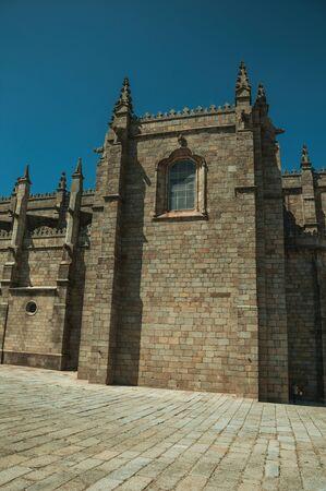 Steinziegelmauer mit Strebepfeilern und Zinnendekoration an einem sonnigen Tag, an der Seite der gotischen Guarda-Kathedrale. Diese freundliche und gepflegte mittelalterliche Stadt ist die höchstgelegene des kontinentalen Portugals. Standard-Bild