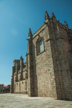 Steinziegelmauer mit Strebepfeilern und Zinnendekoration an einem sonnigen Tag, an der Seite der gotischen Guarda-Kathedrale. Diese freundliche und gepflegte mittelalterliche Stadt ist die höchstgelegene des kontinentalen Portugals.