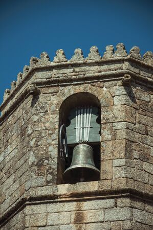 Close-up of stone brick wall and bronze bell in a sunny day, on the steeple top of the gothic Guarda Cathedral. This friendly and well-kept medieval town is the highest in the continental Portugal. Imagens
