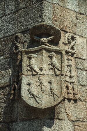 Charming family coat of arms shield carved on stone in a wall of gothic Cathedral, in a sunny day at Guarda. This friendly and well-kept medieval town is the highest in the continental Portugal.