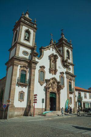 Guarda, Portugal - July 16, 2018. Church of the Misericordia in baroque style and people on a square of Guarda. This friendly and well-kept medieval town is the highest in the continental Portugal.