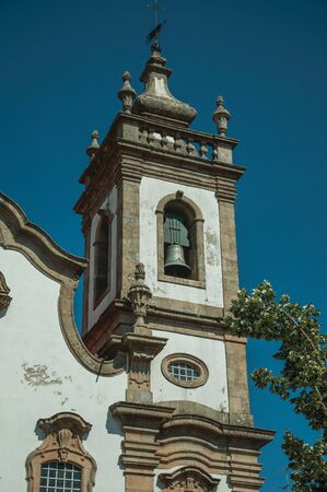Baroque bell tower from church with whitewashed wall and exquisite stone decoration, in a sunny day at Guarda. This friendly and well-kept medieval town is the highest in the continental Portugal. Stok Fotoğraf