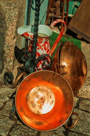 Close-up of copper pans and wrought iron objects on deserted alley, in a sunny day at Guarda. This friendly and well-kept medieval town is the highest in the continental Portugal. Retouched photo.