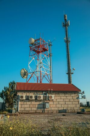 Telecommunication cellular network towers with antennas in a base transceiver station, on sunset at Guarda. This friendly and well-kept medieval town is the highest in the continental Portugal. Banco de Imagens