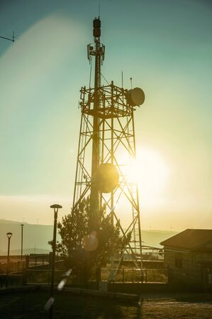 Silhouette of telecommunication tower with antennas and sun flare effect on sunset at Guarda. This friendly and well-kept medieval town is the highest in the continental Portugal. Retouched photo.
