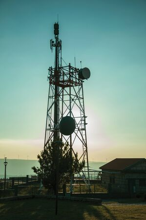 Silhouette of telecommunication metallic tower with antennas in a base transceiver station on sunset at Guarda. This friendly and well-kept medieval town is the highest in the continental Portugal.