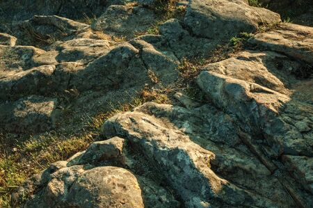 Close-up of eroded rocks with green grass on sunset at Guarda. This friendly and well-kept medieval town is the highest in the continental Portugal.