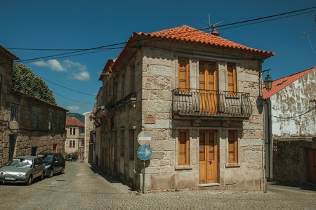Belmonte, Portugal - July 16, 2018. Old house on deserted alley and road signpost, in a sunny day at Belmonte. A cute small town, birthplace of the navigator Pedro Alvares Cabral, on eastern Portugal. Editorial