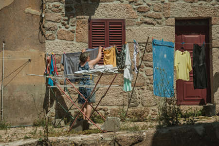 Belmonte, Portugal - July 16, 2018. Old woman hanging clothes to dry in front of old house at Belmonte. A cute small town, birthplace of the navigator Pedro Alvares Cabral, on eastern Portugal.