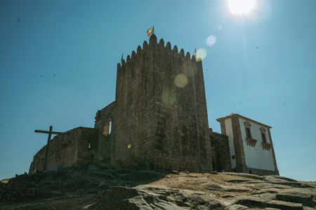 Stone walls and square tower over rocky hill with sunlight at the medieval Belmonte Castle. A small town, birthplace of the navigator Pedro Alvares Cabral, on eastern Portugal.