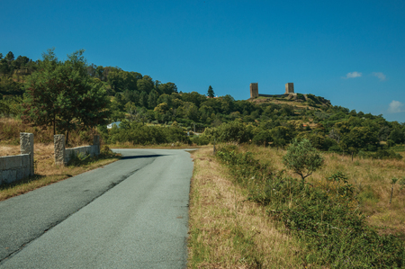 Countryside road passing through hilly landscape with the towers of Linhares da Beira Castle on top. A medieval hamlet with unique architectural diversity fruit of several times, in eastern Portugal. Editorial