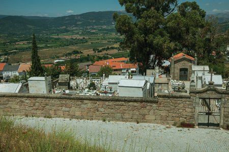 Guarda, Portugal - July 16, 2018. Cemetery with walls and iron gate encircling tombs and crypts in Belmonte. A cute small town, birthplace of the navigator Pedro Alvares Cabral, on eastern Portugal.