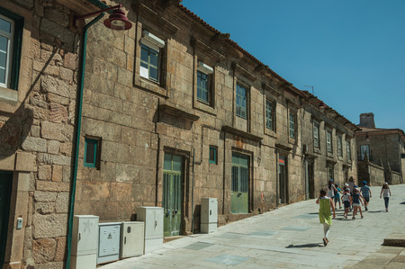 Guarda, Portugal - July 16, 2018. People walking next to charming long building made of stone at Guarda. This friendly and well-kept medieval town is the highest in the continental Portugal. Editorial