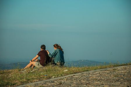 Guarda, Portugal - July 16, 2018. Couple of young people sitting on lawn with hilly landscape on sunset at Guarda. This friendly and well-kept medieval town is the highest in the continental Portugal.