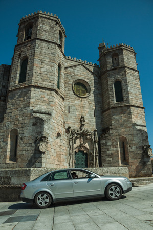 Guarda, Portugal - July 16, 2018. Car in front of gothic Cathedral with steeples, in a sunny day at Guarda. This friendly and well-kept medieval town is the highest in the continental Portugal. Editorial