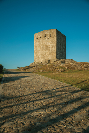 Stone square tower over rocky hill with lawn and deserted pathway, on sunset at Guarda. This friendly and well-kept medieval town is the highest in the continental Portugal.
