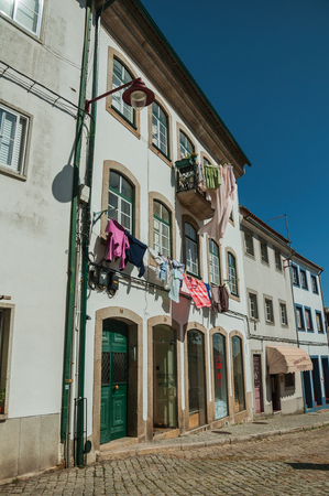 Guarda, Portugal - July 16, 2018. Clothes hung to dry in front of windows on baroque building at Guarda. This friendly and well-kept medieval town is the highest in the continental Portugal.