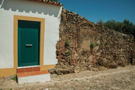 Closed door in a plaster white wall next to a stone and bricks wall in sunny day, from a street of Evoramonte. A tiny fortified civil parish over hill where stands out its historic castle in Portugal.