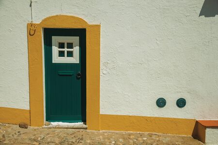Green wooden door in a white wall on sunny day, from a cobblestone street of Evoramonte. A tiny fortified civil parish over hill where stands out its historic castle in Portugal. Retouched photo.