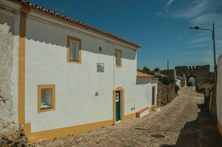 Green wooden doors in white wall house on sunny day, from a cobblestone street of Evoramonte. A tiny fortified civil parish over hill where stands out its historic castle in Portugal.
