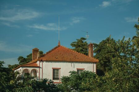 Rooftop of charming cottage amidst lush green trees on sunset in a small farm near Elvas. A gracious star-shaped fortress city on the easternmost frontier of Portugal.