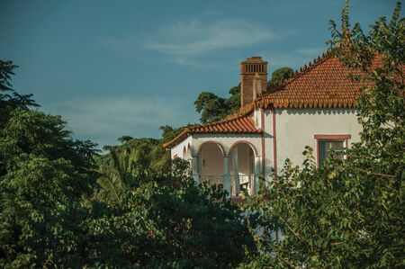 Rooftop and terrace of charming cottage amidst lush green trees on sunset in a small farm near Elvas. A gracious star-shaped fortress city on the easternmost frontier of Portugal.